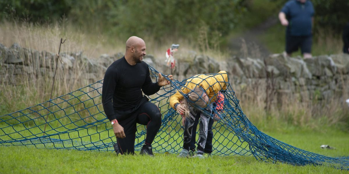 A father and daughter coming out from underneath a scramble net