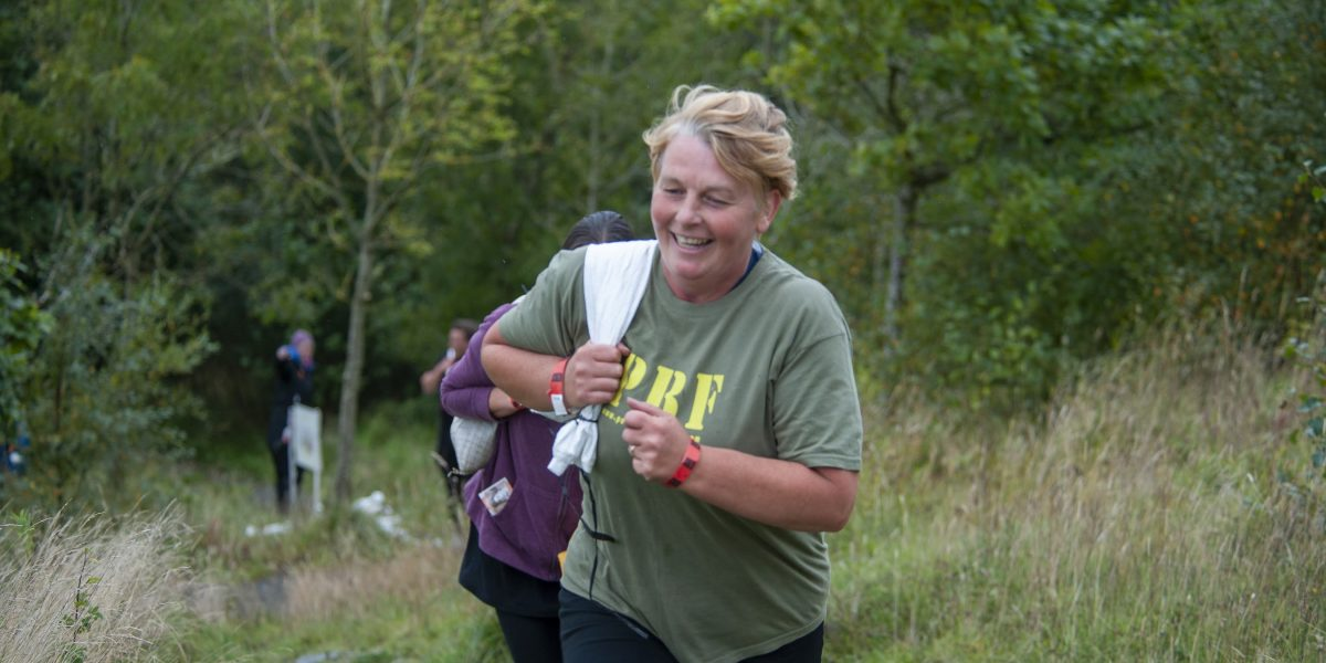 Two women running on a countryside trail carrying sandbags