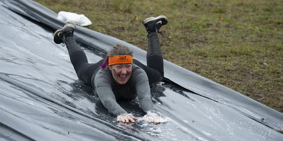 A woman wearing a orange headband going down a water slide
