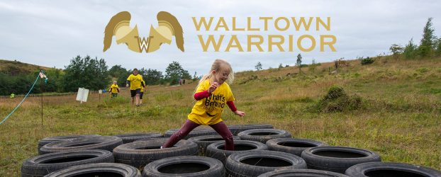 A young girl running over a set of tyres with a walltown warrior logo above