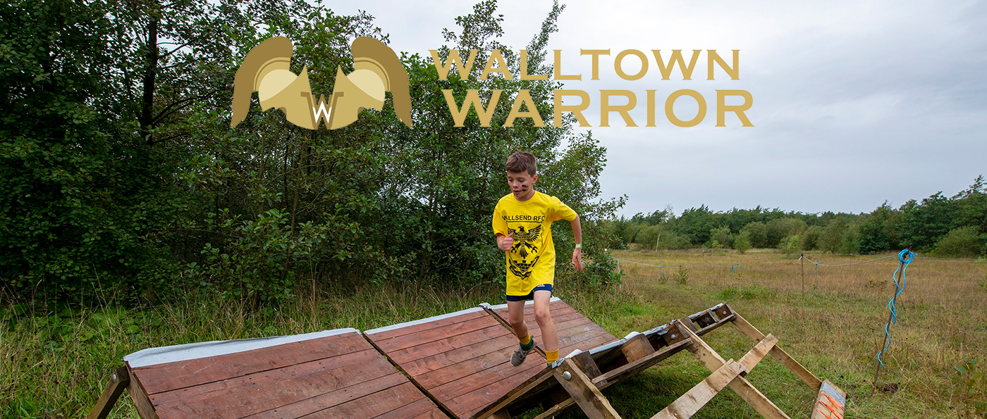 A young boy running over a wooden obstacle with a walltown warrior logo above