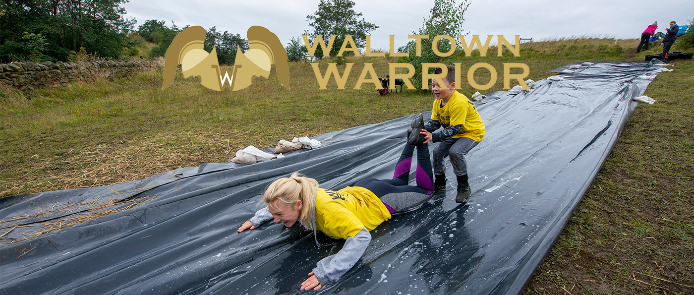 A mother and son going down a water slide with a walltown warrior logo above