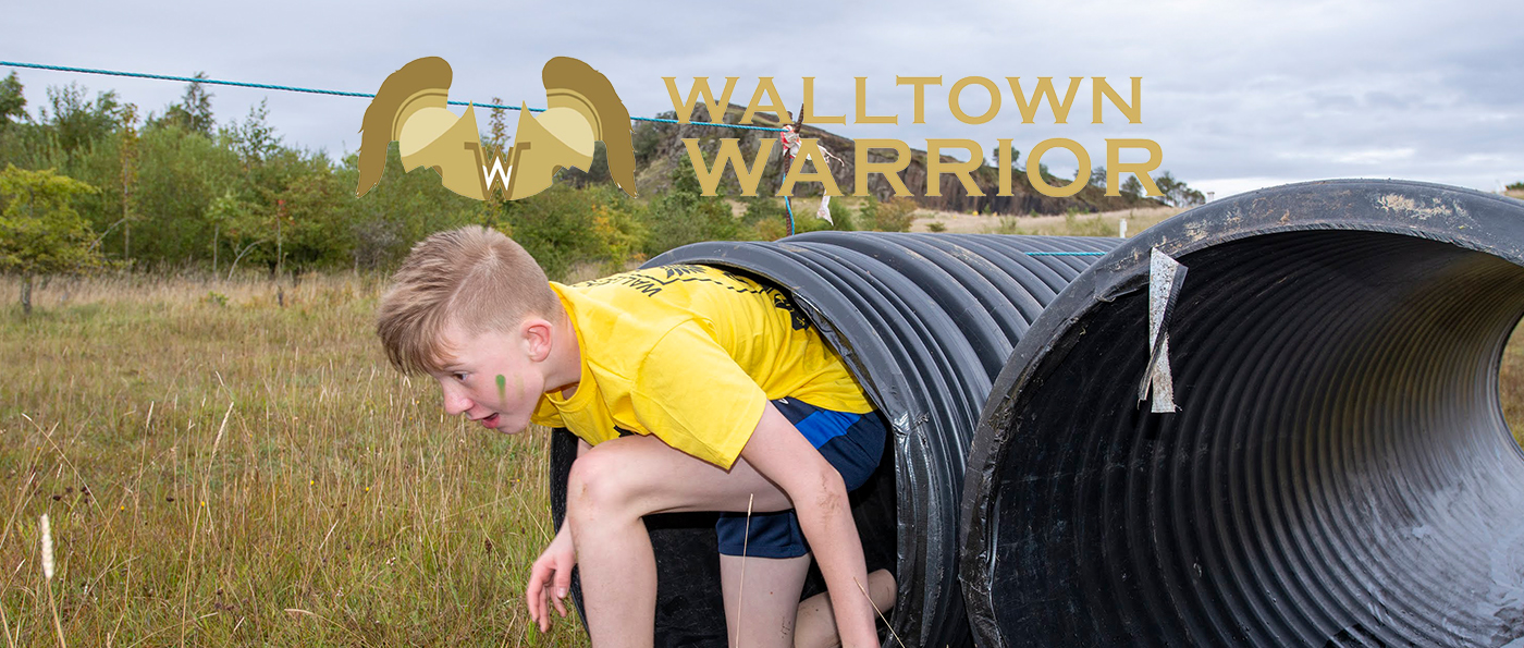A young boy emerging from a tunnel with a walltown warrior logo above