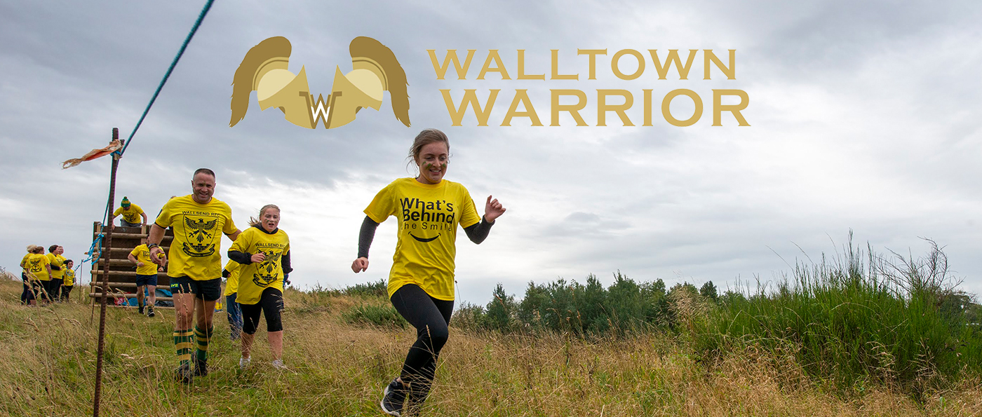 A young of young men and women running with a walltown warrior logo above