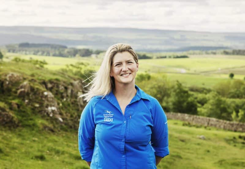 Senior Ranger Margeret Anderson took in front of a countryside backdrop, wearing a cyan coloured National Park uniform