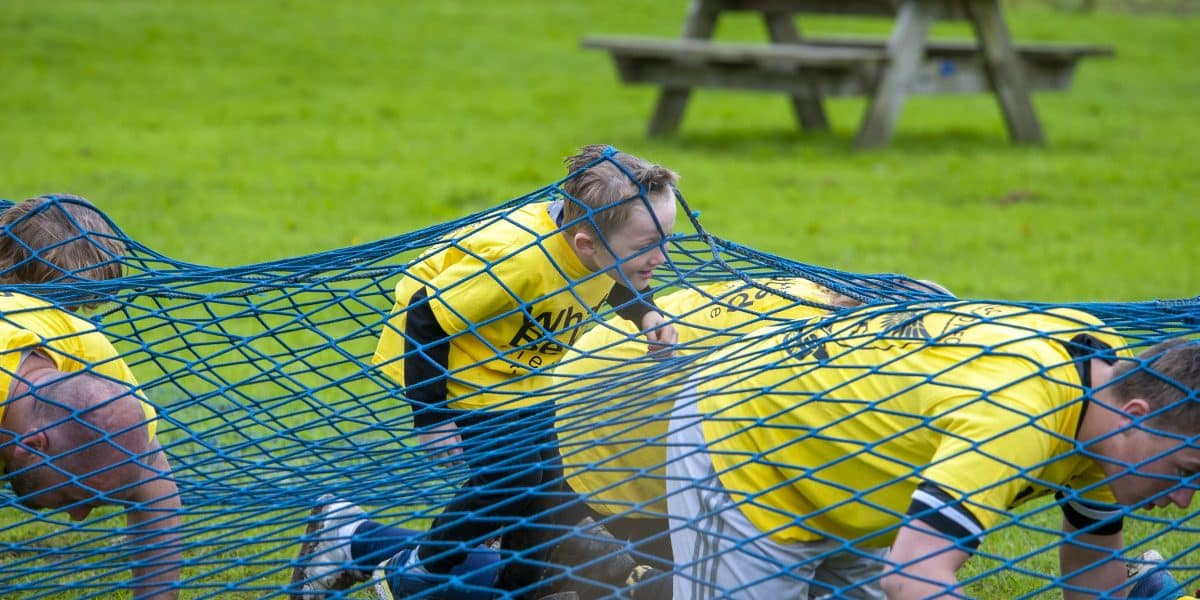 A young biy and several adults make their way through a blue scramble net as part of an obstacle course