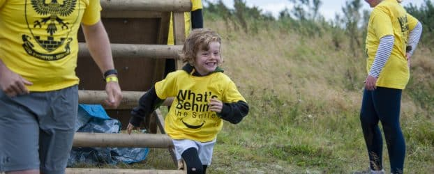 A young boy runs with a smile on his face away from a wooden ladder at Walltown Country Park while taking part in an obstacle course.