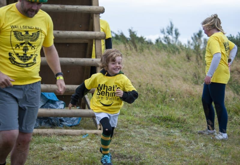 A young boy runs with a smile on his face away from a wooden ladder at Walltown Country Park while taking part in an obstacle course