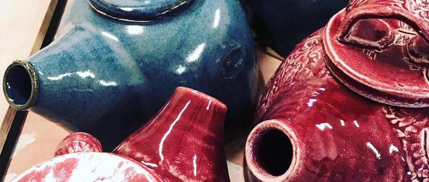 A small collection of blue and red, handmade, teapots