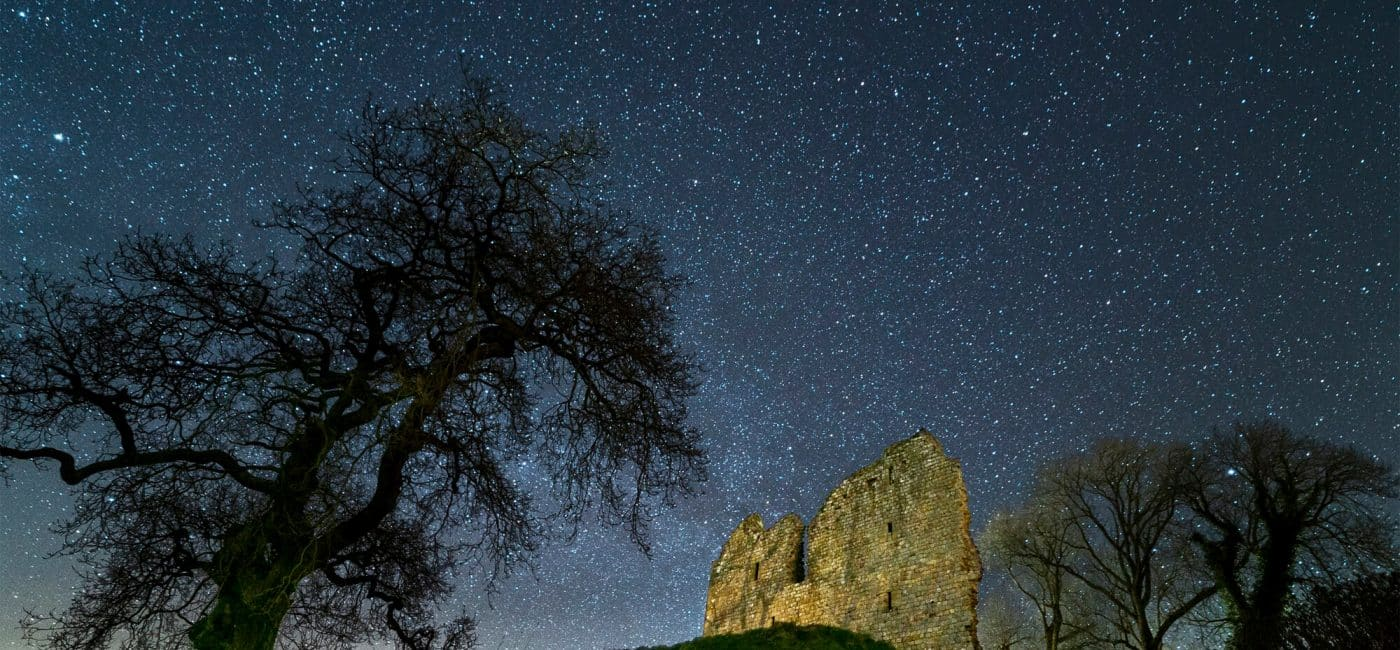 The ruin of Thirlwall Castle stands beside a dark tree on a top of a grass covered hill. The sky is dark and filled with hundreds of stars.
