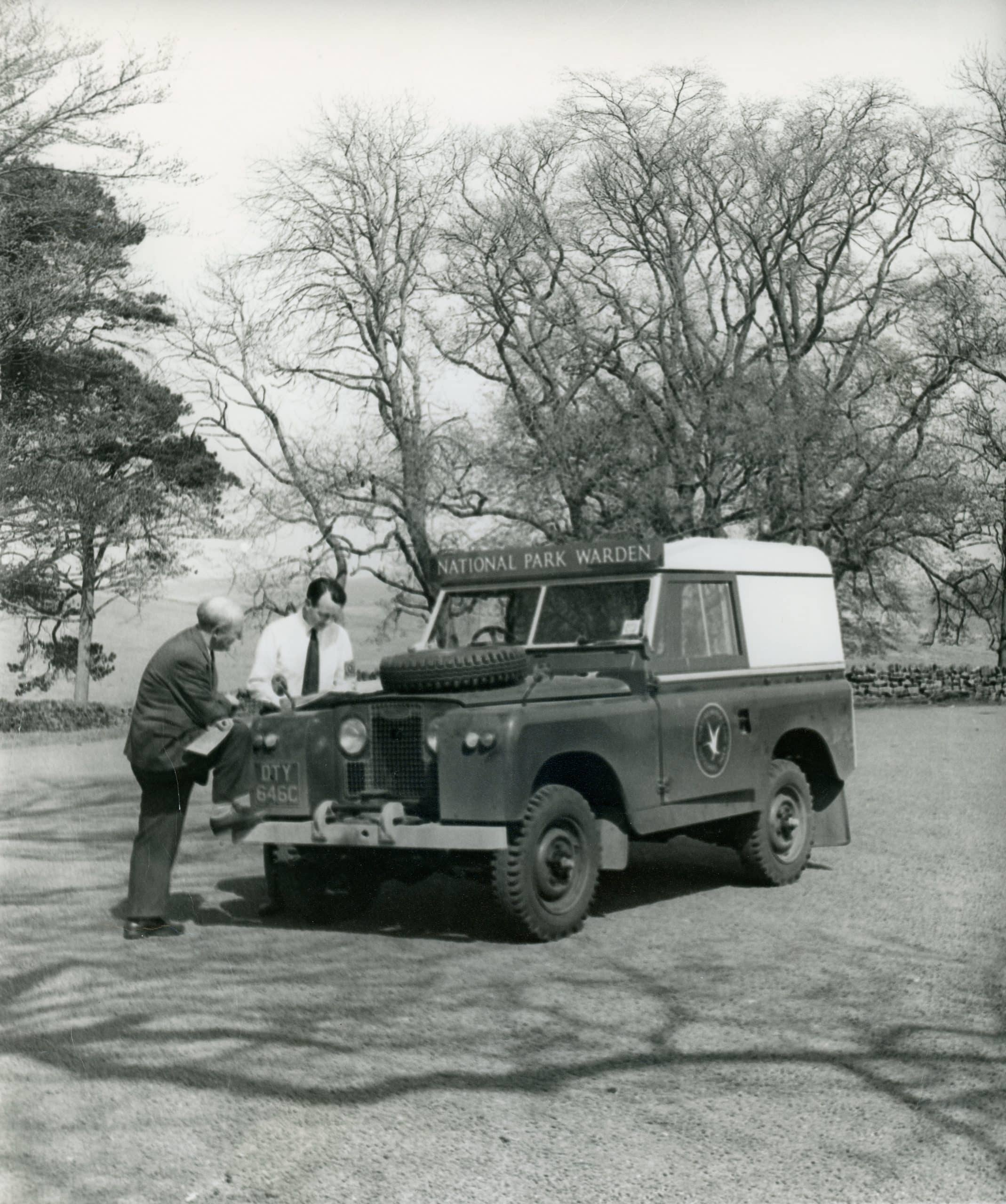 A black and white photograph of a ational Park Warden Jeep with two Rangers stood beside it