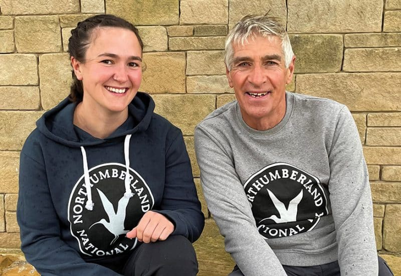 A woman and man model a jumper and hoodie in front of a stone wall